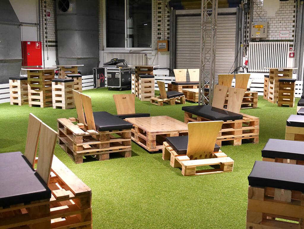 Palettensitzbänke und -tische in einer Halle auf Kunstrasen