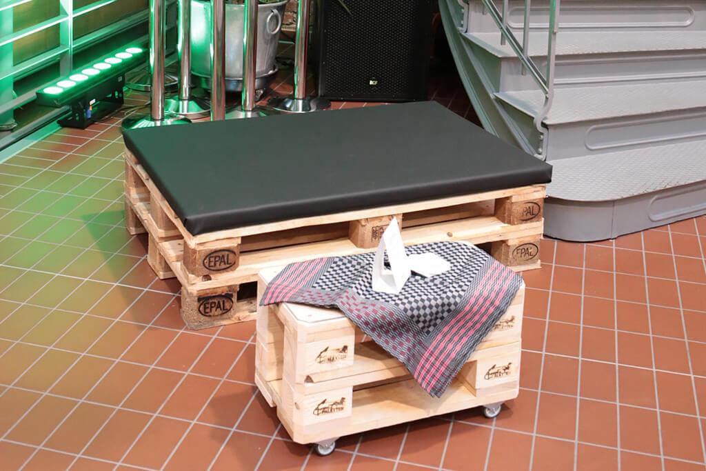 Palette mit Sitzkissen neben einer Treppe