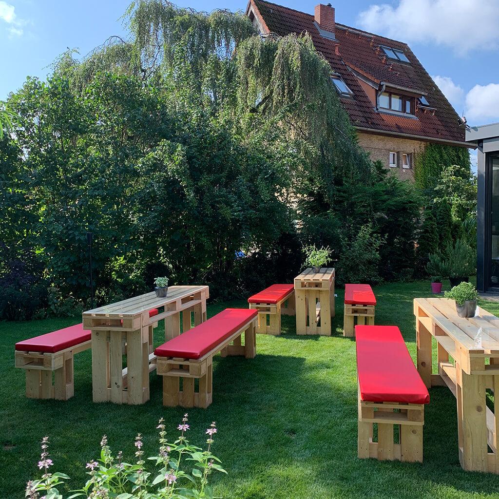Sitzbänke und Tische aus Europaletten in einem Garten